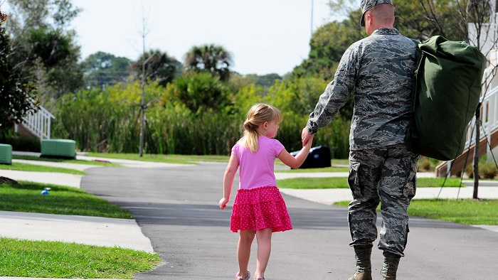 A father and daughter hold hands walking
