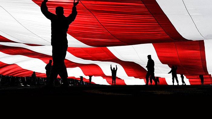 Service members holding up a flag
