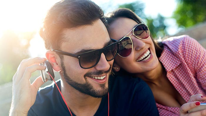 A couple listening to headphones together and smiling
