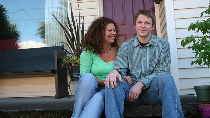 Couple smiles while sitting on their porch