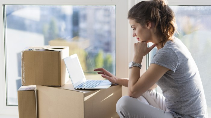 Woman working on laptop on top of moving boxes