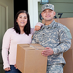 Two service members with a moving box