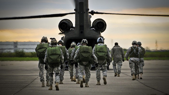 Service members walking towards helicopter