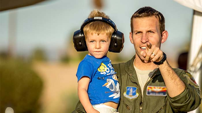 A service member holding their child