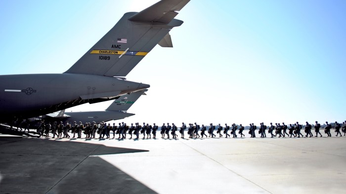 Service members departing from an airplane
