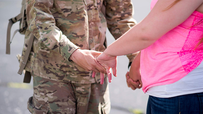 A service member holding hands with fiance