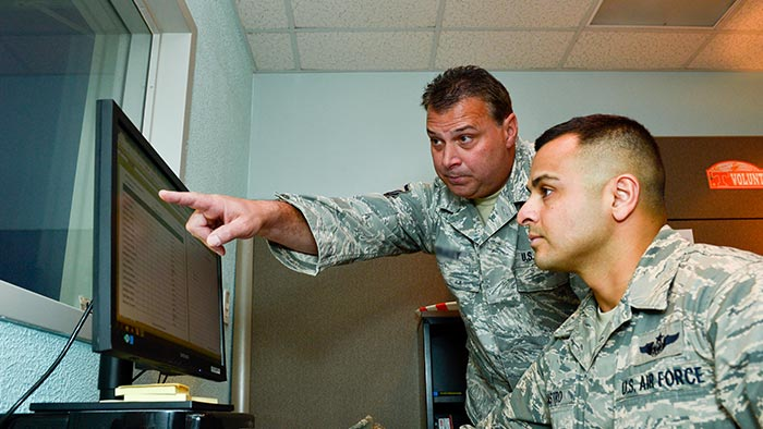 Service members looking at a laptop computer