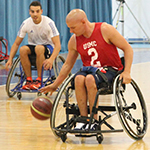 A service member playing basketball in a wheelchair