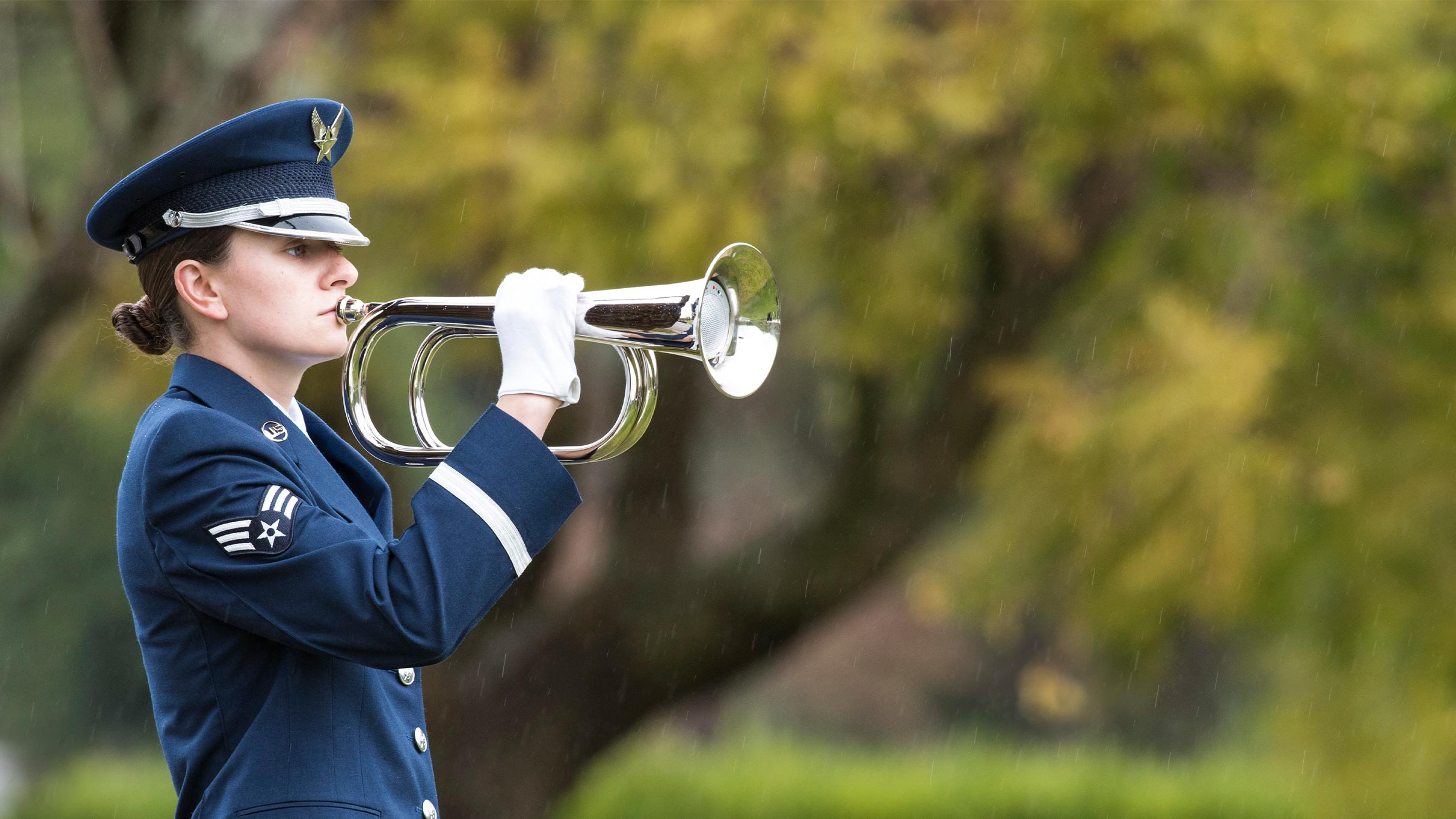 Female Airman plays Taps with a bugle during a U.S. Air Force funeral.