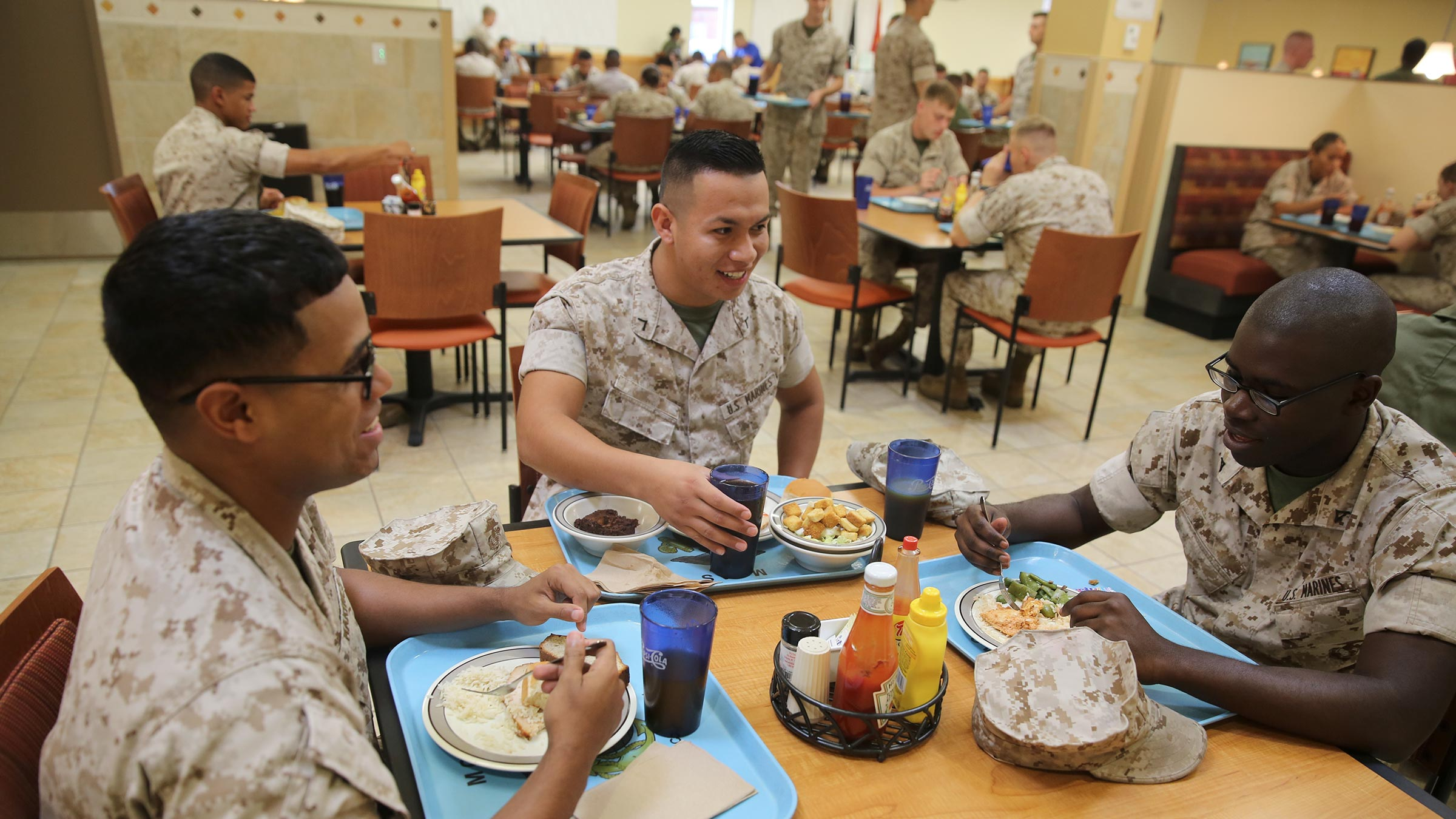 Newly-recruited Marines eat a meal at a mess hall table.