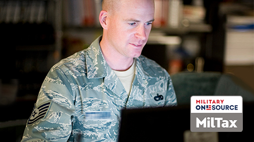 Service member using a laptop with MilTax logo on image