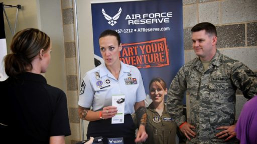 Two service members speak with a woman