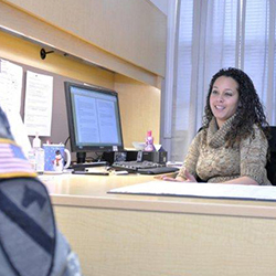 Servicemember speaking with counselor at her desk