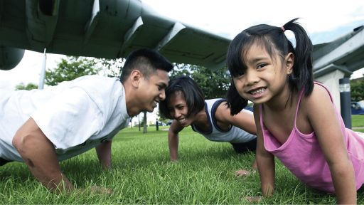 Family of three doing pushups