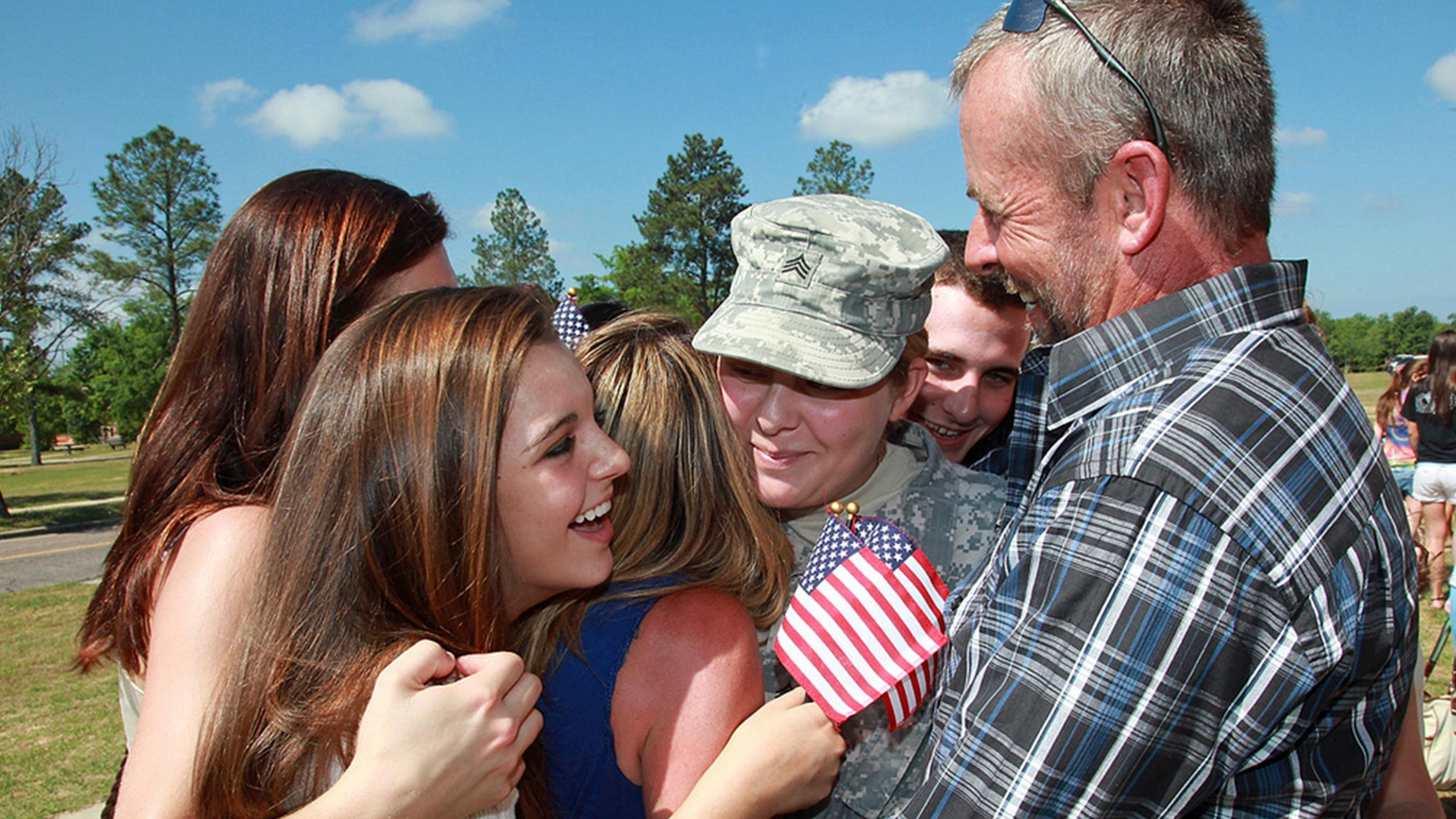 a family surrounds a service member upon her return from deployment