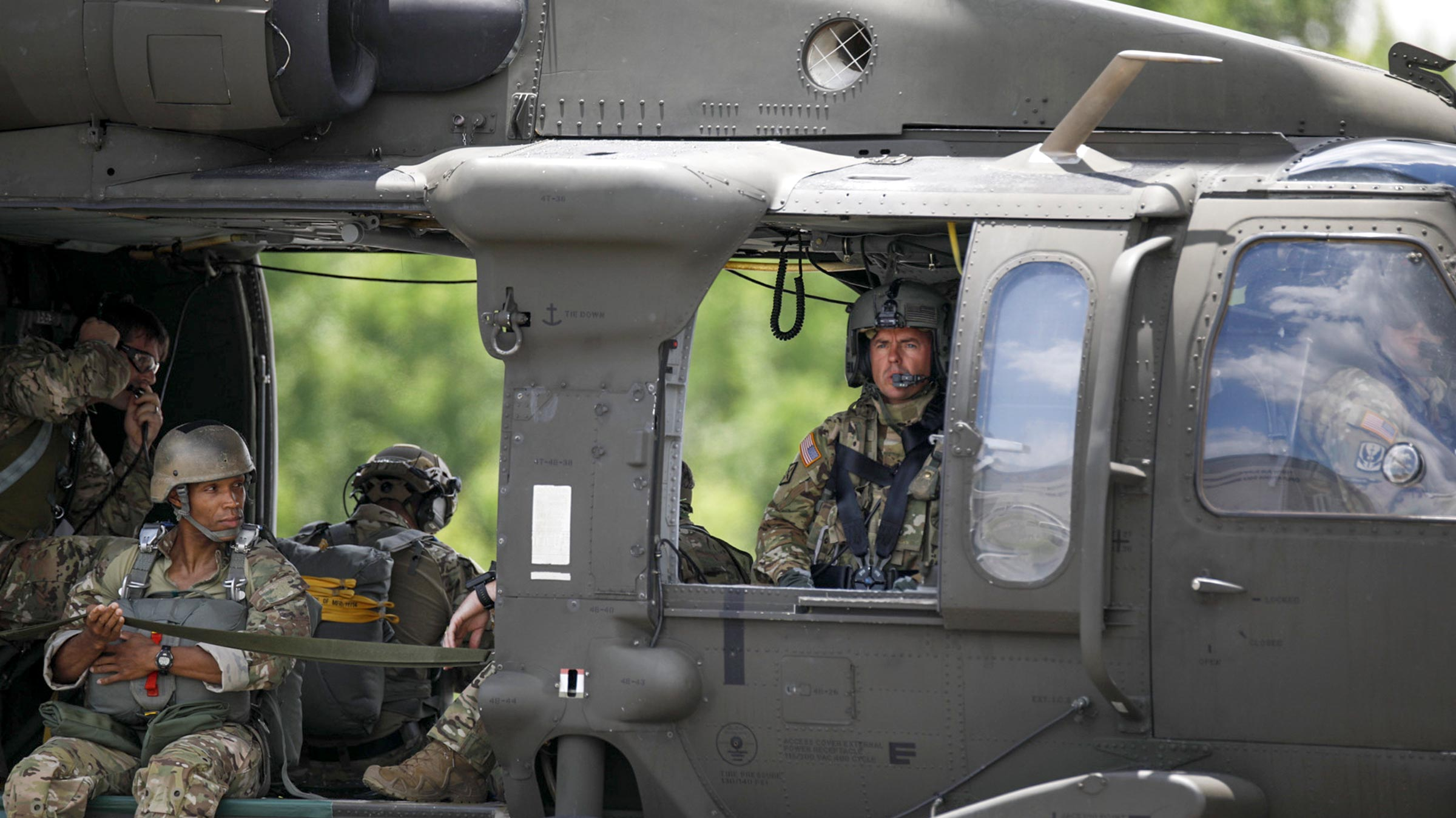 members of the national guard ride in a helicopter