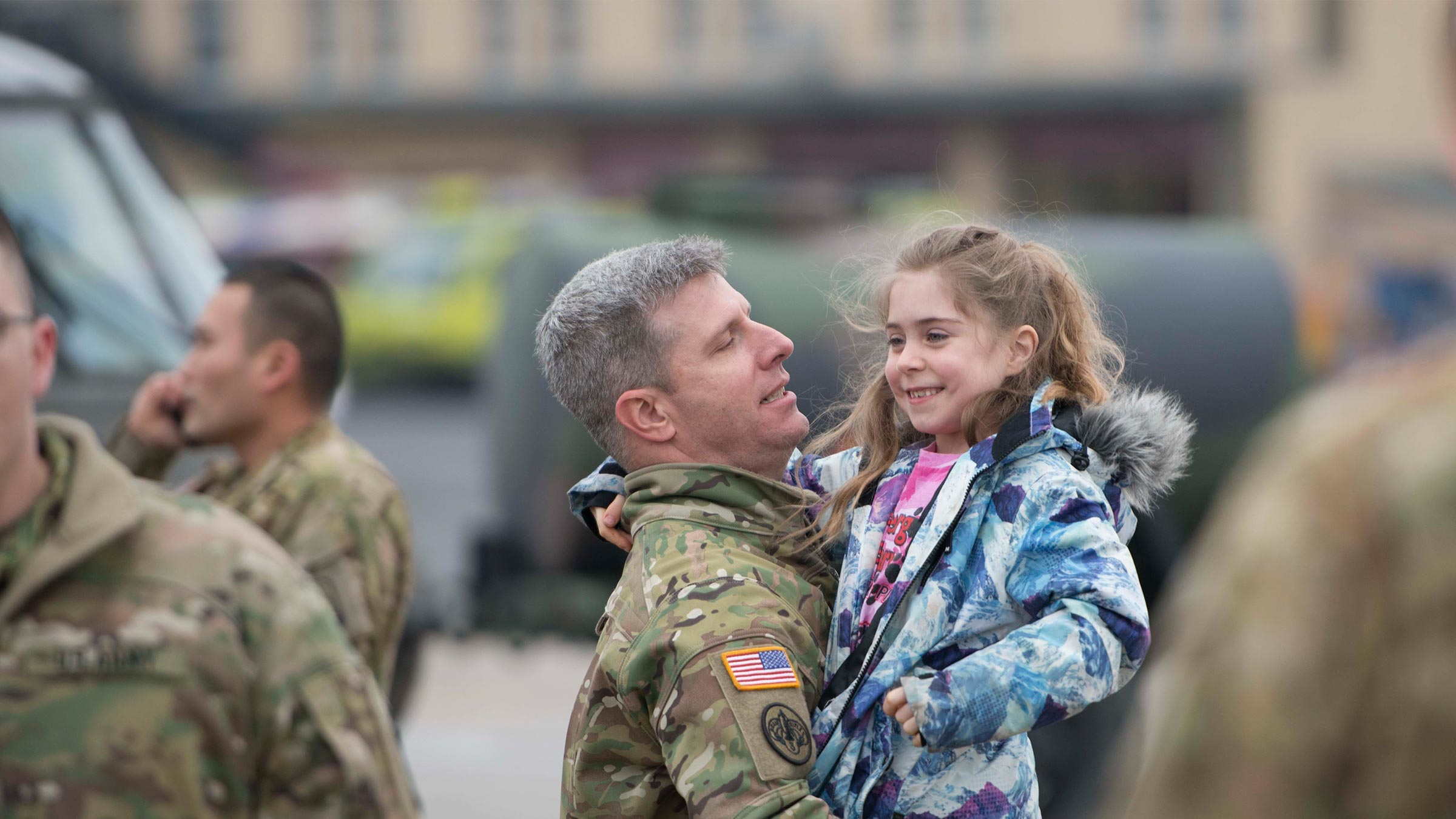 A service member greets his young daughter
