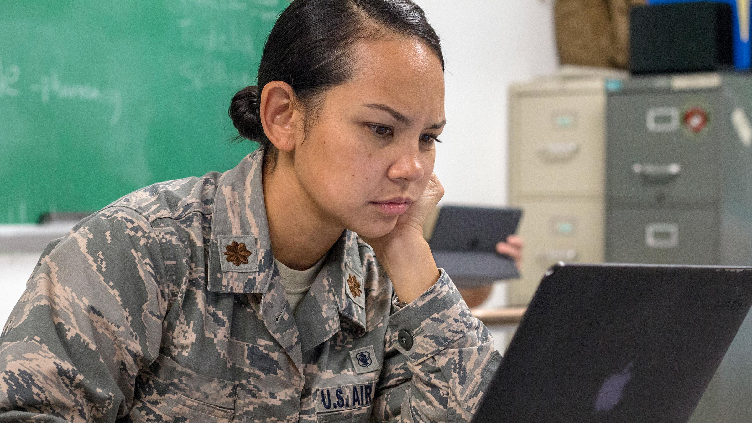 Service member works on her laptop.