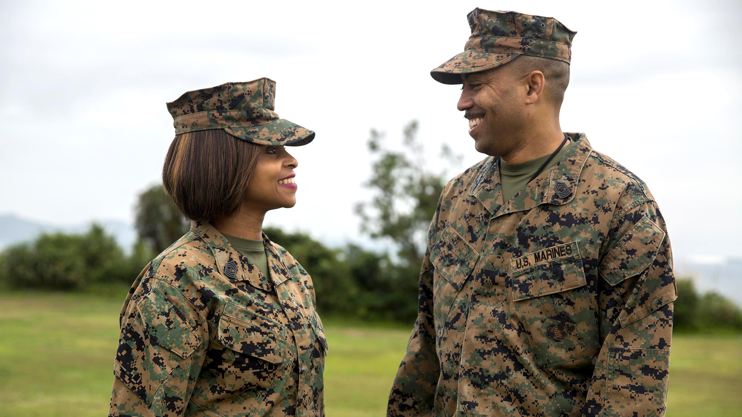 Marine couple smiles at one another.