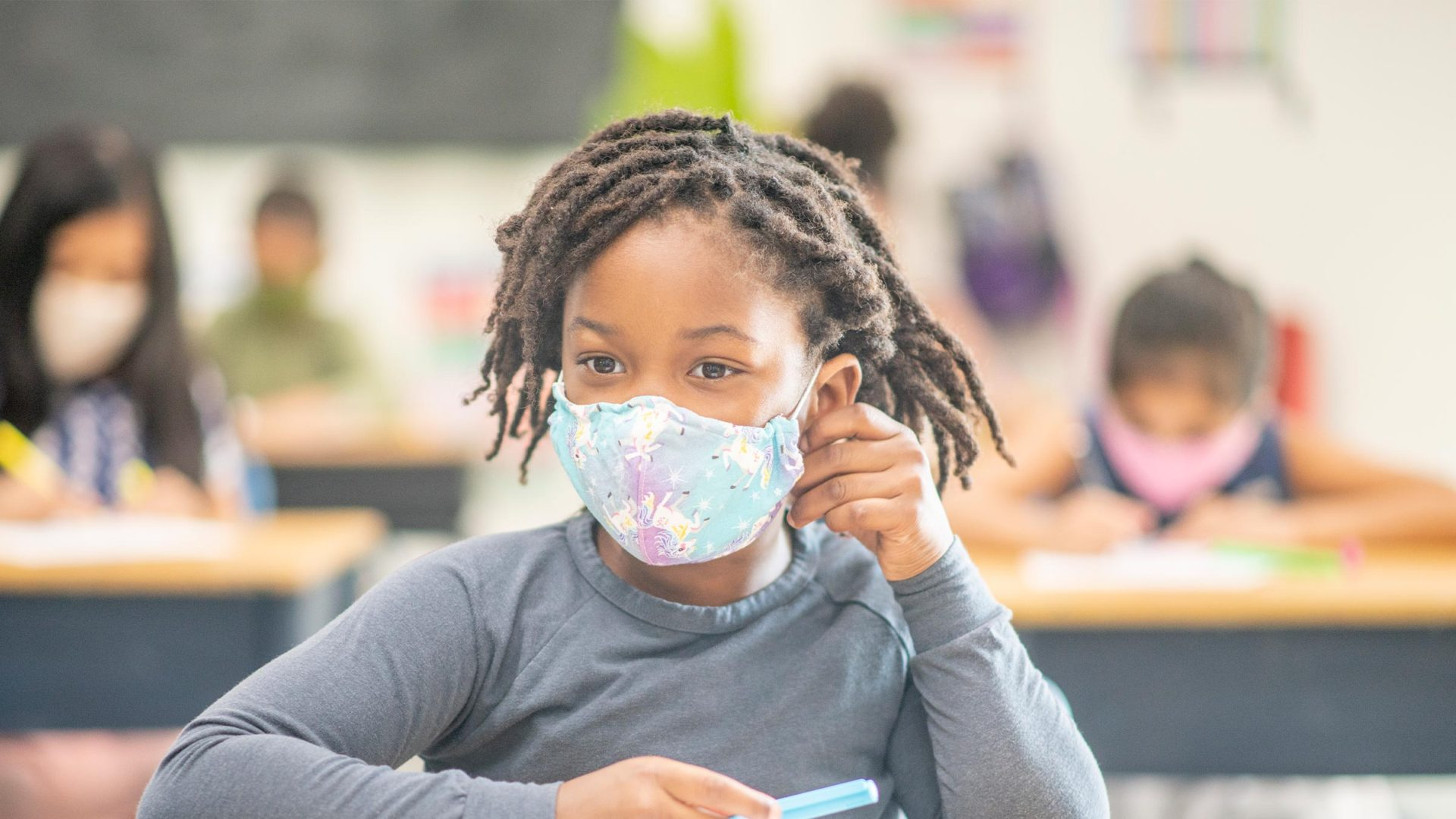 Young girl wearing face mask in school.