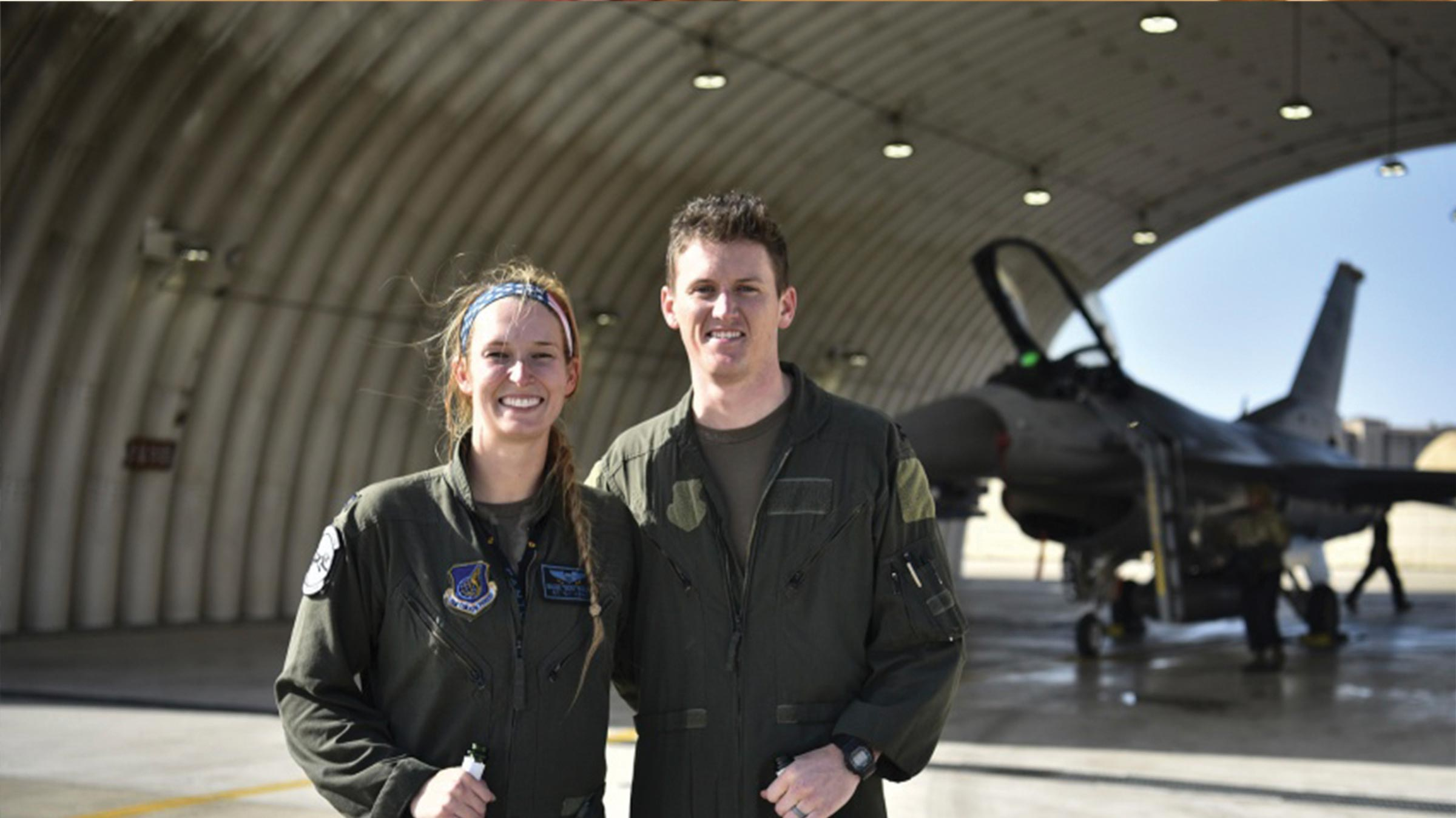 Couple stand in airplane hanger