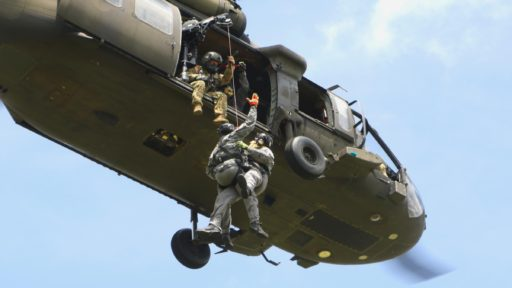 service members drop from helicopter.