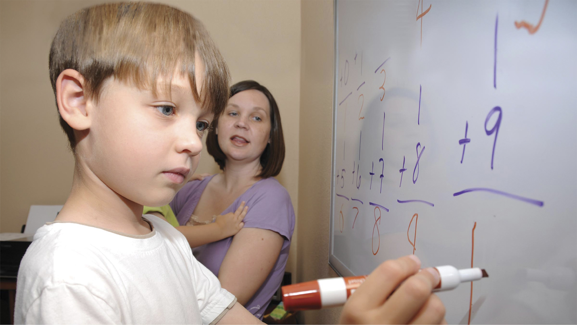 Child writing on whiteboard with mom looking on