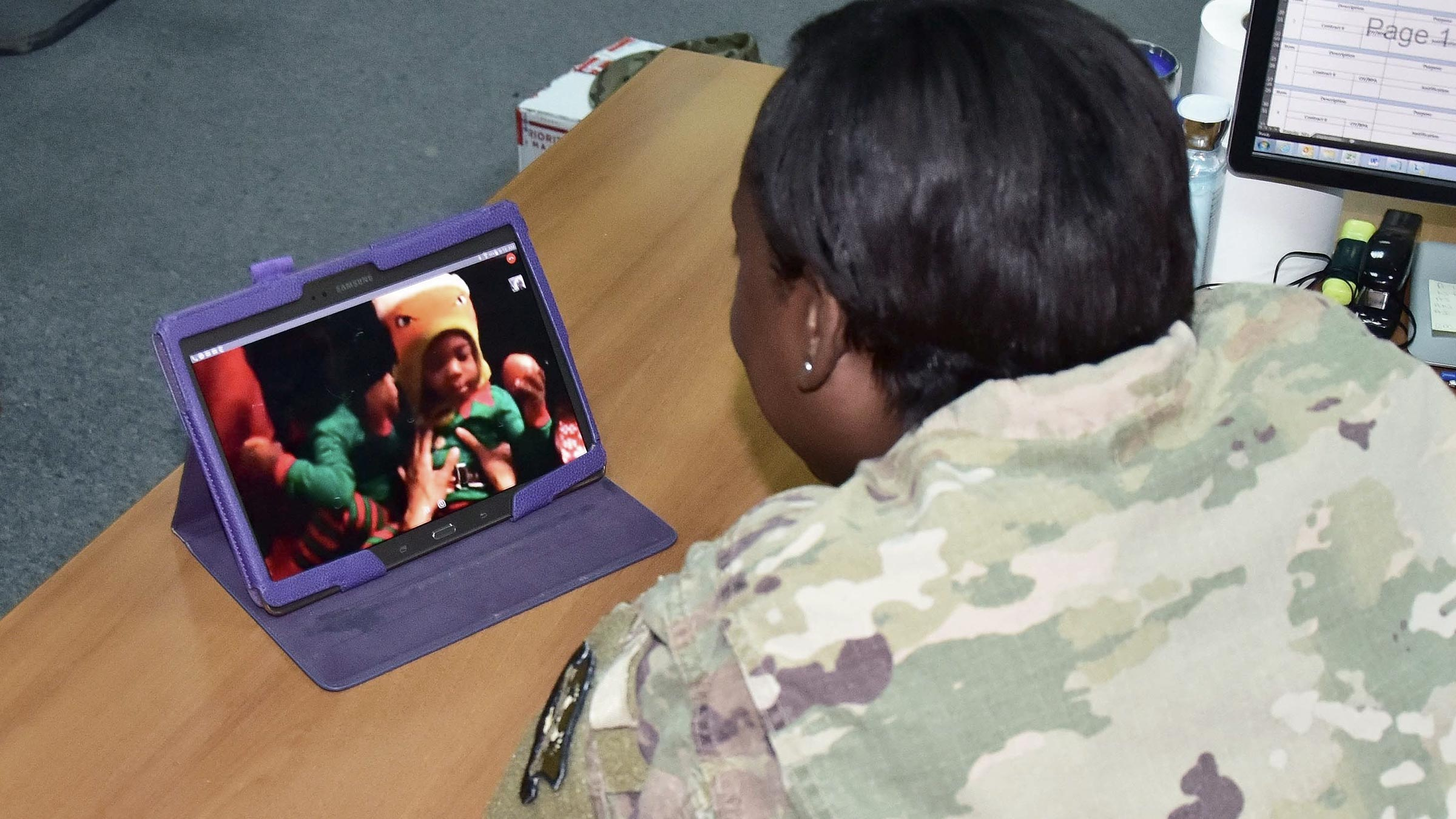 A service member watches her children open presents via video chat.
