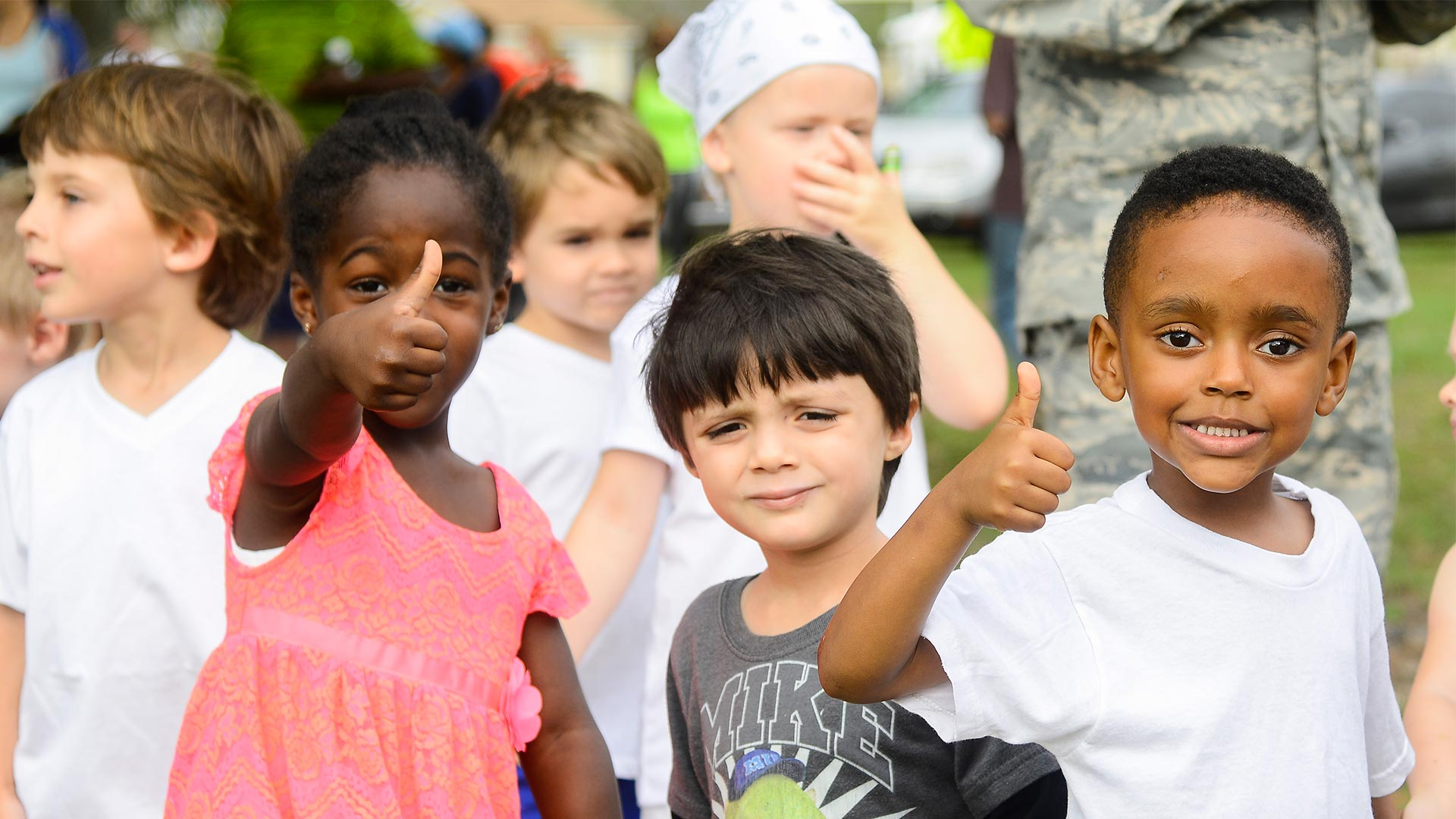 Young children give a thumbs up