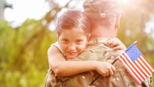 Military dad holds smiling daughter