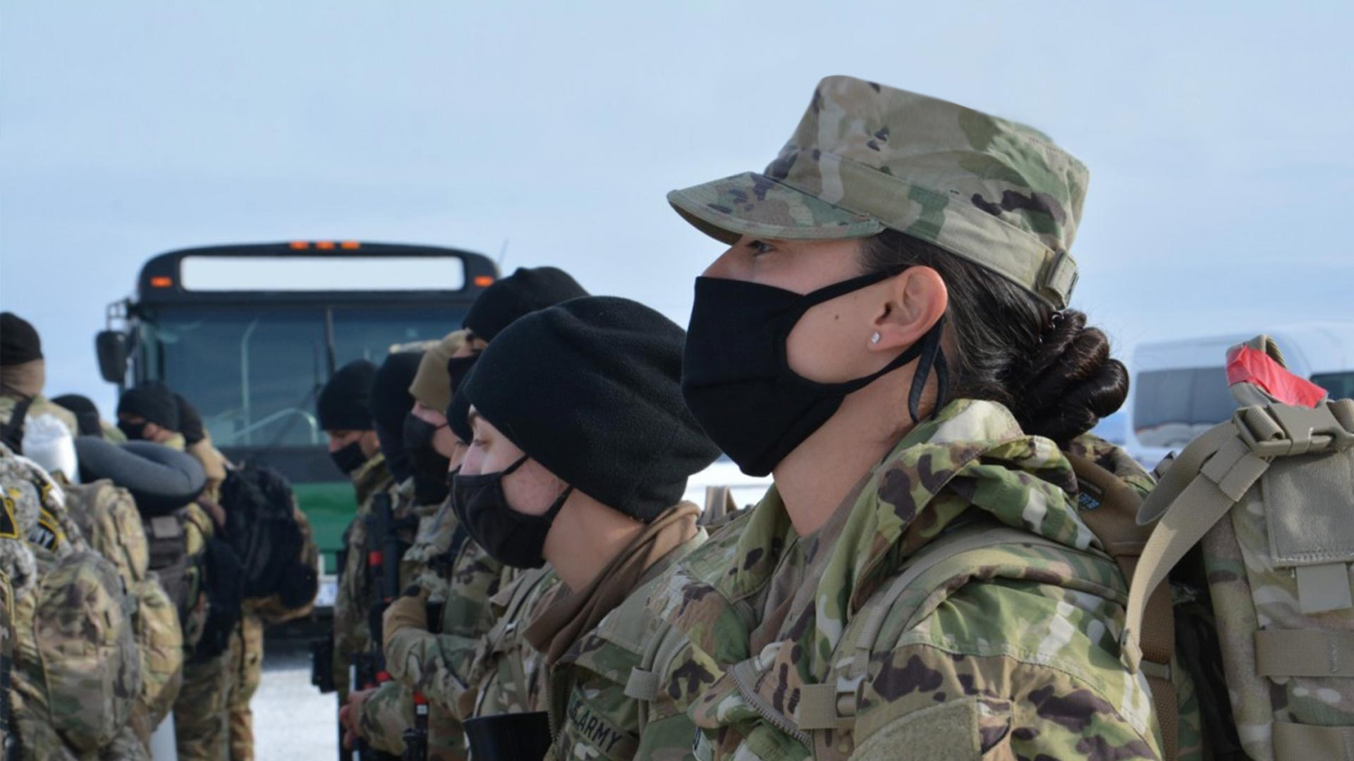 Masked service members waiting to load bus