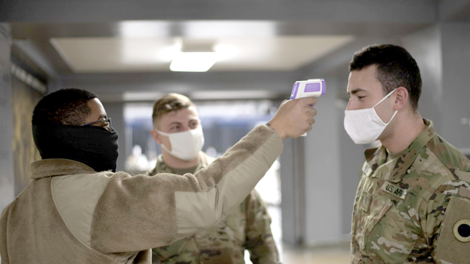 Three men with face masks watch temperature check on service member