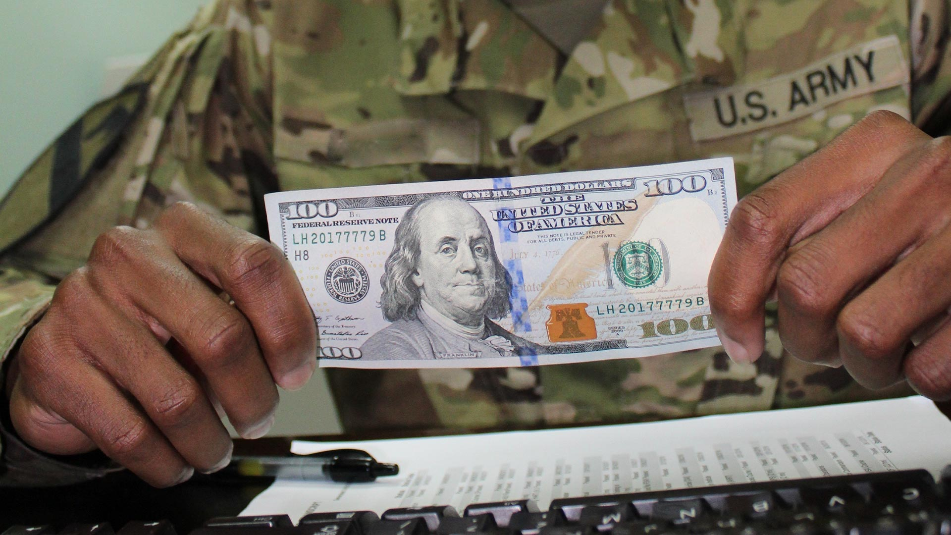 Soldier holds one hundred dollar bill