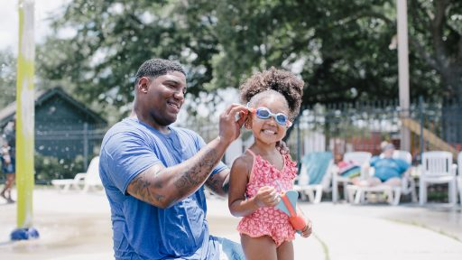 Father helping daughter with goggles