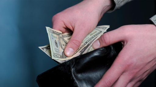 Hands holding cash and wallet