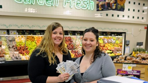 Two women hold coupons at the grocery store