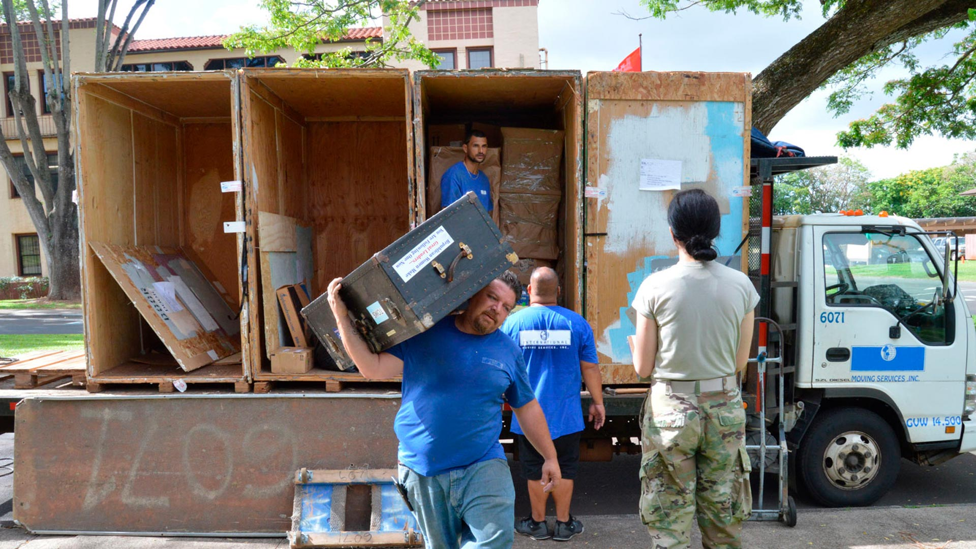 Army soldier relocating, movers unloading truck